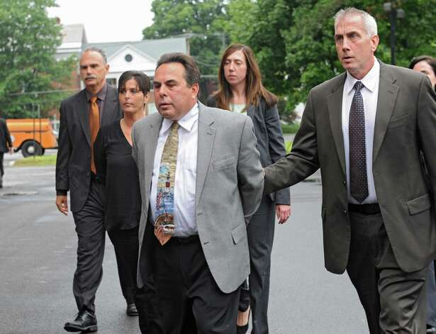 Bruce Tanski's secretary Katina Fogarty, second from left, and Nicholas DiNova Jr., third from left,  an employee of Troy Sand & Gravel who lives in a home Tanski built, are brought to the Saratoga County Courthouse in custody by FBI agents and state attorney generals investigators Friday, Aug. 22, 2014 in Ballston Spa, N.Y. The two were being charged with a single count of concealing the true origin of a campaign donation. Bruce Tanski, a prominent Halfmoon builder, was arrested by State Police on charges alleging he paid employees and business associates to make political contributions to the campaign account of Melinda Wormuth, a former Halfmoon town supervisor. (Lori Van Buren / Times Union) Photo: Lori Van Buren / 00028289A