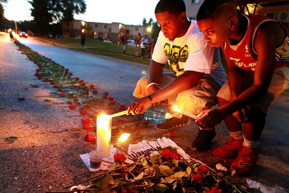 Theo Murphy (left) and brother Jordan Marshall visit a memorial in Ferguson, Mo., for Michael Brown, the unarmed teen who was shot by a police officer. Photo: Christian Gooden, Associated Press