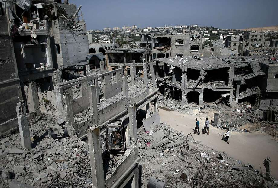 Palestinian civilians walk past destroyed buildings in the northern Gaza Strip city of Beit Hanun. Photo: Thomas Coex, AFP/Getty Images