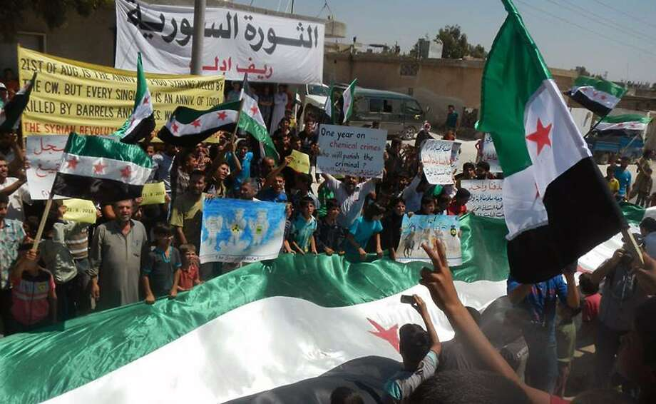 Antigovernment demonstrators carry banners and a giant revolutionary flag during a demonstration against President Bashar Assad in Idlib province, northern Syria. Photo: Uncredited, Associated Press