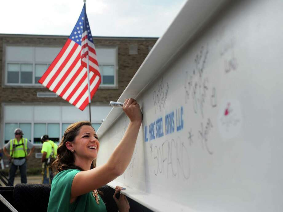 Jillian Soto signs the final beam before it is set in place on the Victoria Soto School at Stratford Academy Thursday, Aug. 21, 2014 in Stratford, Conn. Victoria Soto, a teacher and lifelong Stratford resident, was killed in the Sandy Hook Elementary School shooting. Photo: Autumn Driscoll / Connecticut Post