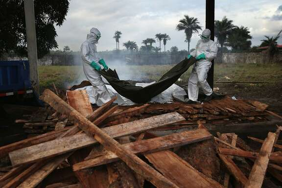 MARSHALL, LIBERIA - AUGUST 22:  A burial team from the Liberian Ministry of Health unloads the bodies of Ebola victims onto a funeral pyre at a crematorium on August 22, 2014 in Marshall, Liberia. The Ebola epidemic has killed at least 1,350 people in West Africa and more in Liberia than any other country.  (Photo by John Moore/Getty Images) *** BESTPIX ***