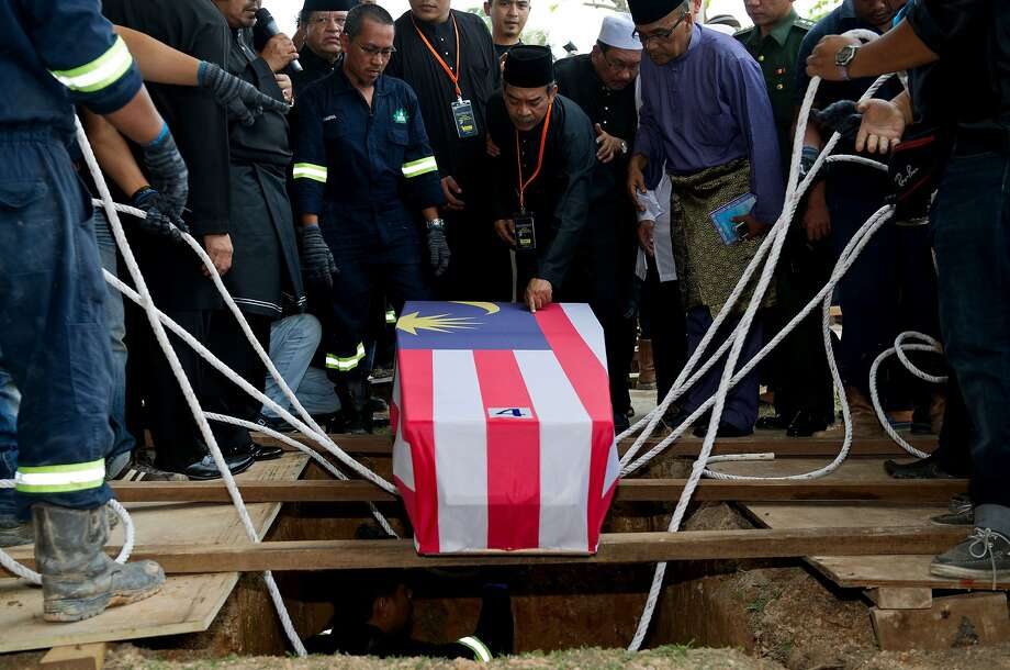 TOPSHOTS Mohamed Salleh, (C) the father of Malaysia Airlines flight attendant Nur Shazana, one of the Malaysians who perished aboard flight MH17 that was downed in eastern Ukraine, touches her coffin during a burial ceremony in Putrajaya, outside Kuala Lumpur on August 22, 2014.  Black-clad Malaysians paused for a minute of silence Friday on a nationwide day of mourning held to sombrely welcome home the first remains of its 43 citizens killed in the MH17 disaster. AFP PHOTO / MOHD RASFANMOHD RASFAN/AFP/Getty Images Photo: Mohd Rasfan, AFP/Getty Images