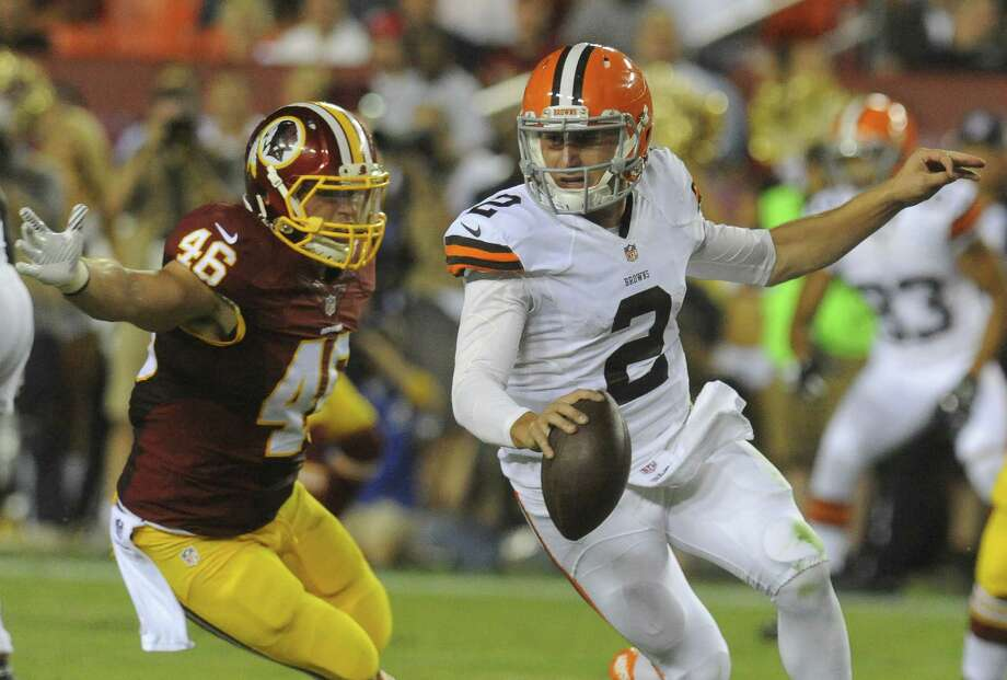 "Cleveland Browns quarterback Johnny Manziel, shown here trying to elude a defender on Monday night, raised a furor for hurling something besides a football — a middle finger salute. A reader says he is tired of hearing people make excuses for the ""spoiled brat."" Photo: Richard Lipski / Associated Press / FR170623 AP"