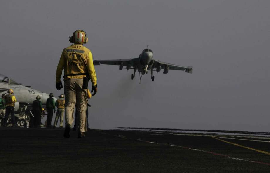 An EA-6B coming from Iraq lands on the flight deck of the USS George H.W. Bush earlier this month in the Persian Gulf. Aircraft aboard the carrier are flying missions over Iraq after President Barack Obama authorized airstrikes against Islamic militants and food drops for trapped Iraqis. Photo: Hasan Jamali / Associated Press / AP