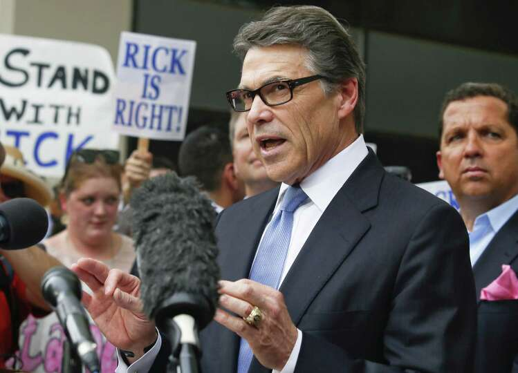 Gov. Rick Perry addresses supporters and the media as his lawyer Tony Buzbee (right) looks on. A rea