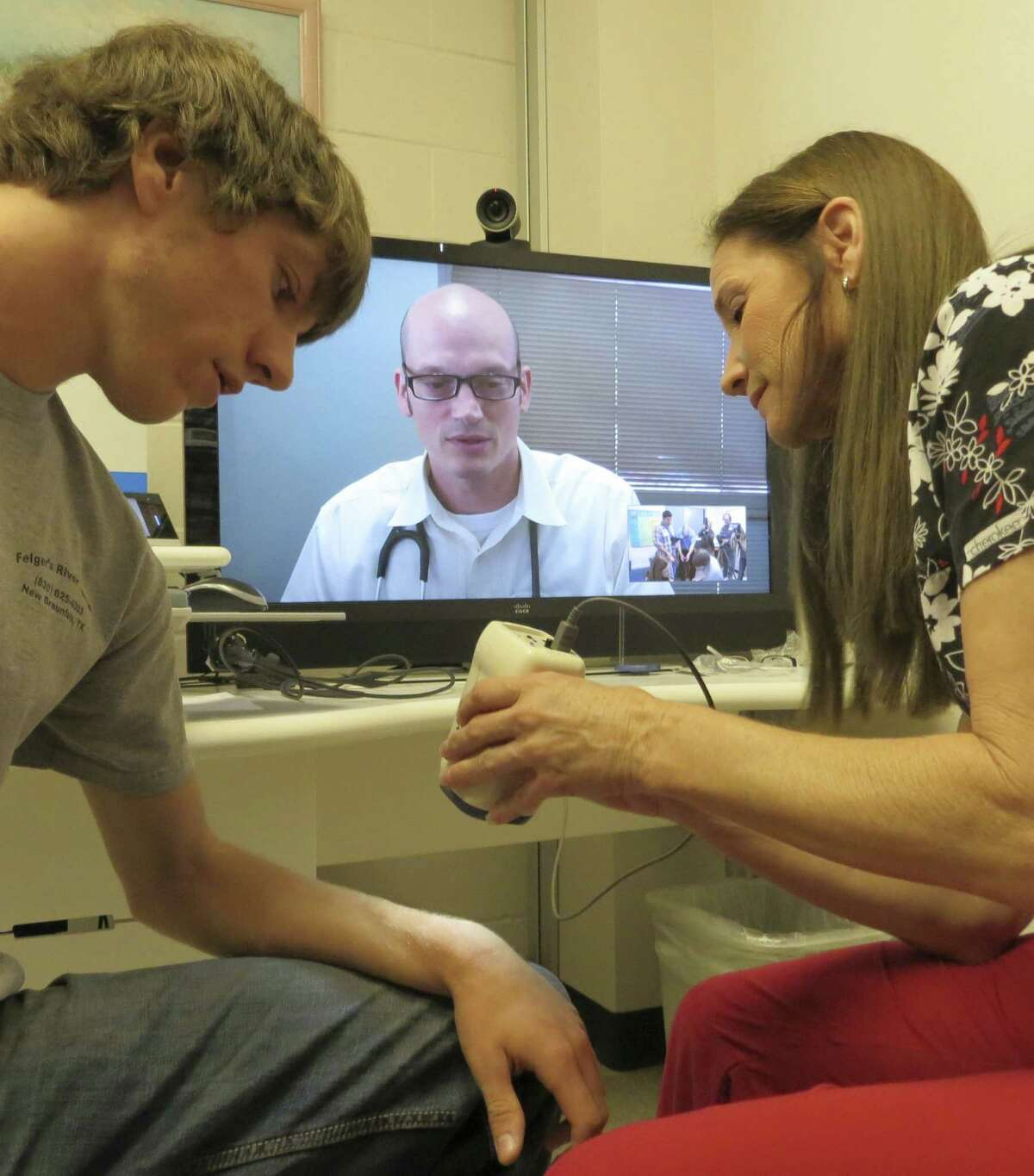 Canyon High School Nurse Regina Smith uses a scope to let Dr. Robert Morin remotely examine a student's arm.