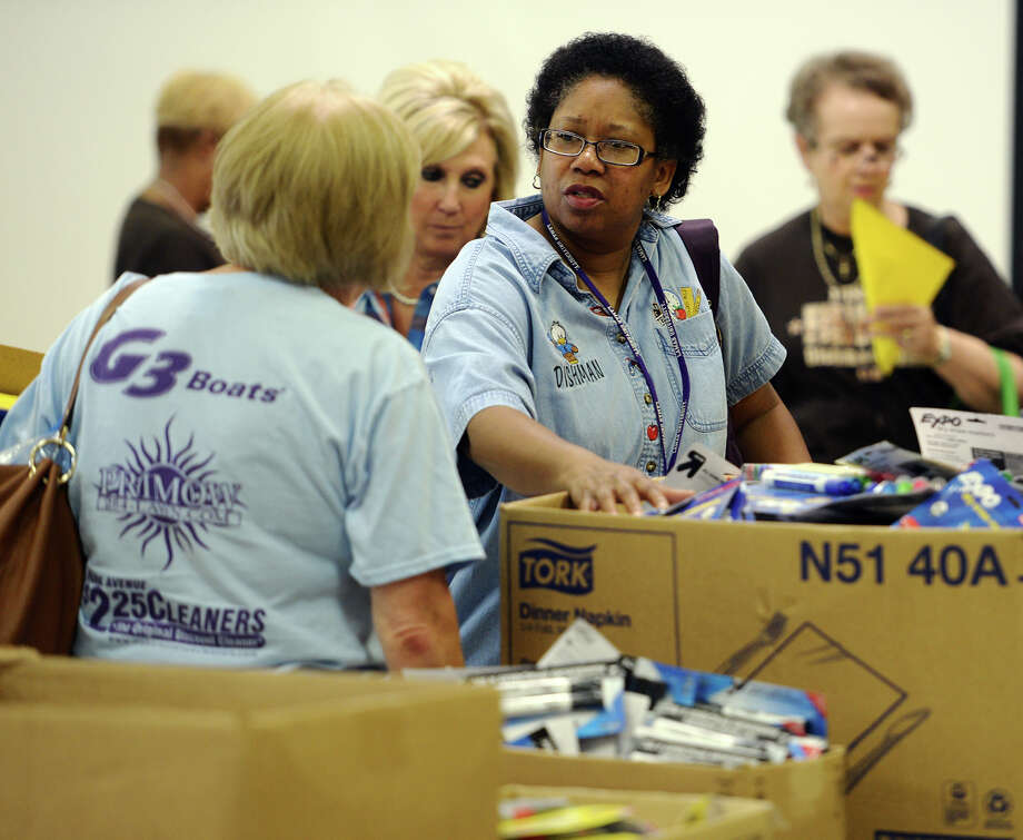 Barbara Garrett, front, a special education teacher at Dishman Elementary, talks with Veronica Holmes, a Dishman kindergarten teacher, as they shop through classroom supplies Friday morning. The Adopt a BISD Teacher program gave away school supplies to teachers on Friday morning. Sarah Sanders, a former West Brook student, said the group raised $25,000 to spend on teaching supplies, and that computers at stores where they shopped kept crashing due to the bulk orders. Teachers were allotted 35 points to spend on supplies, which were organized and given point values in relation to their price.  Photo taken Friday 8/22/14 Jake Daniels/@JakeD_in_SETX Photo: Jake Daniels / ©2014 The Beaumont Enterprise/Jake Daniels