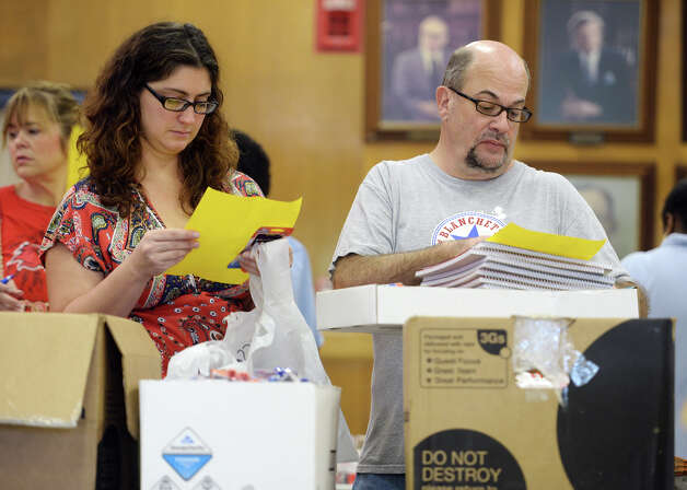 Amber Schmoll, left, and Kyle Calame, both first grade teachers at Blanchette Elementary, look over their point lists as they shop for classroom supplies Friday morning. The Adopt a BISD Teacher program gave away school supplies to teachers on Friday morning. Sarah Sanders, a former West Brook student, said the group raised $25,000 to spend on teaching supplies, and that computers at stores where they shopped kept crashing due to the bulk orders. Teachers were allotted 35 points to spend on supplies, which were organized and given point values in relation to their price.  Photo taken Friday 8/22/14 Jake Daniels/@JakeD_in_SETX Photo: Jake Daniels / ©2014 The Beaumont Enterprise/Jake Daniels