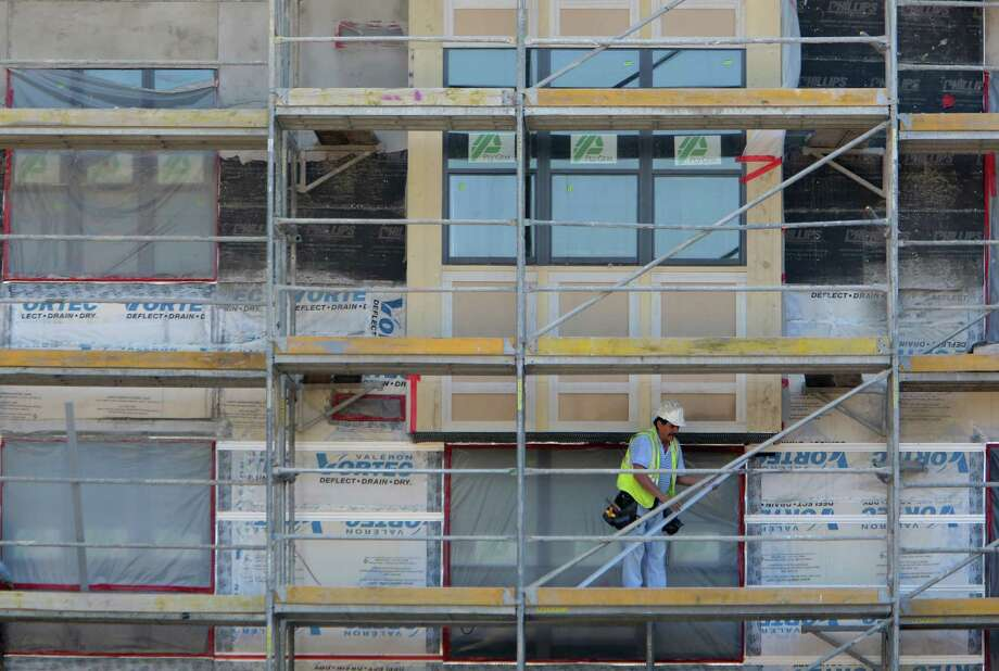 The construction crew works at The Susanne, a luxury apartment complex, construction site on Wednesday, Aug. 13, 2014, in Houston.  ( Mayra Beltran / Houston Chronicle ) Photo: Mayra Beltran, Staff / © 2014 Houston Chronicle