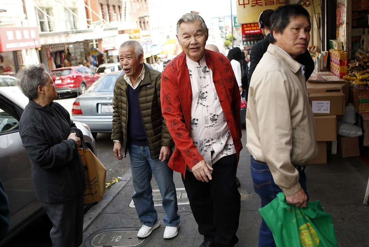 Artist Frank Wong (second from right) walks through Chinatown in San Francisco, Calif. on Tuesday, August 19, 2014.