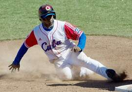 (FILES) This October 24, 2011 file photo shows Cuban Rusney Castillo as he arrives on third base, during a match against the US, in the XVI Panamerican Games in Lagos de Moreno, State of Jalisco,  Mexico.  Rusney Castillo, a Cuban outfielder who defected to Haiti six months ago, has agreed to a record Major League Baseball contract with the Boston Red Sox, multiple reports said August 22, 2014. The league's website and ESPN reported that the Red Sox won a bidding war for the talented 27-year-old Caribbean standout, the latest defector from the Communist island to make his way to the US major leagues. AFP PHOTO/Raul ARBOLEDARAUL ARBOLEDA/AFP/Getty Images