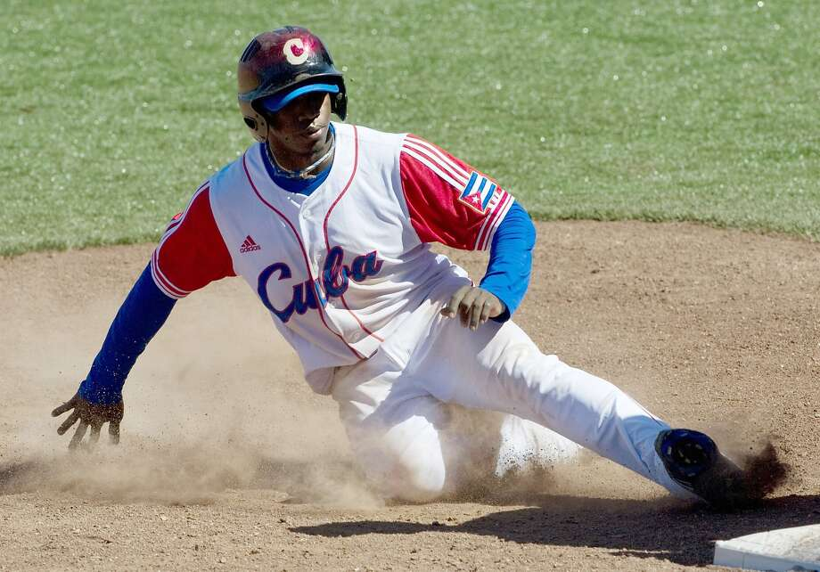 Rusney Castillo slides into third base during a 2011  contest against the U.S. in the  Pan American Games in Mexico. Photo: Raul Arboleda, AFP/Getty Images