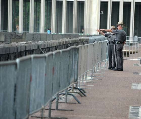 New York State troopers are seen looking at The Wellington Hotel Annex on Howard Street from under the Egg at the Empire State Plaza on Friday, Aug. 22, 2014 in Albany, N.Y. The building is set to be imploded Saturday morning at around 9:30 a.m. Spectators might be able to view the implosion from this spot. (Lori Van Buren / Times Union) Photo: Lori Van Buren / 00028306A