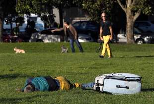 A man sleeps in Duboce Park dog play area in San Francisco, Calif. on Thursday, August 21, 2014.