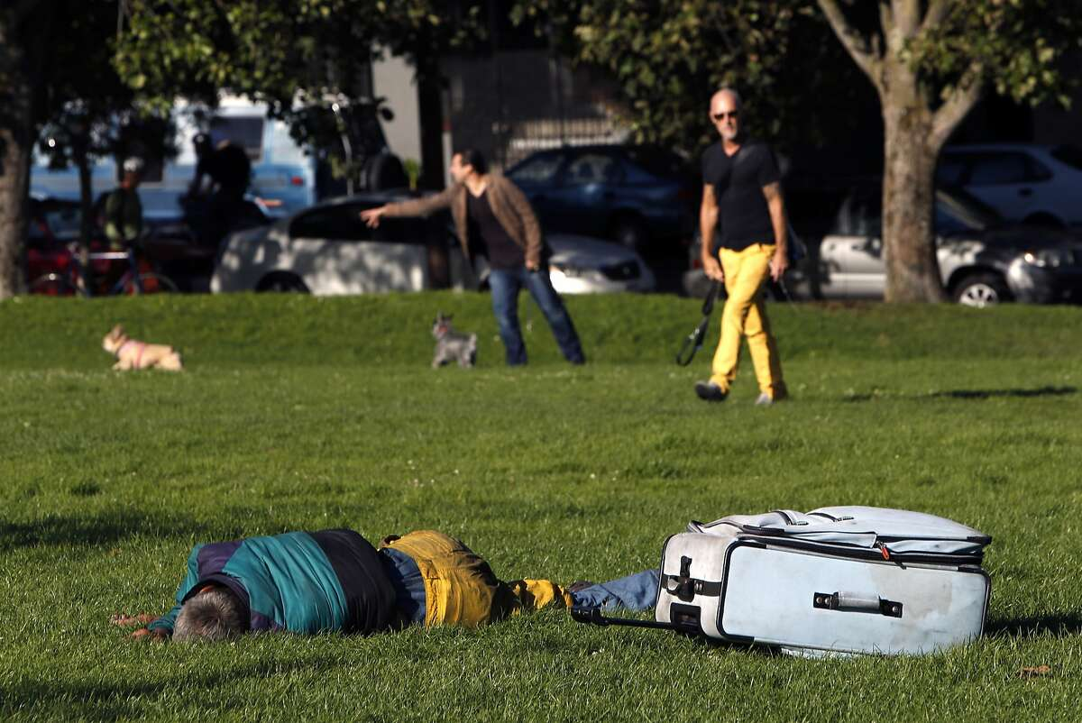 A man sleeps in Duboce Park dog play area in San Francisco, Calif. on Thursday, August 21, 2014.