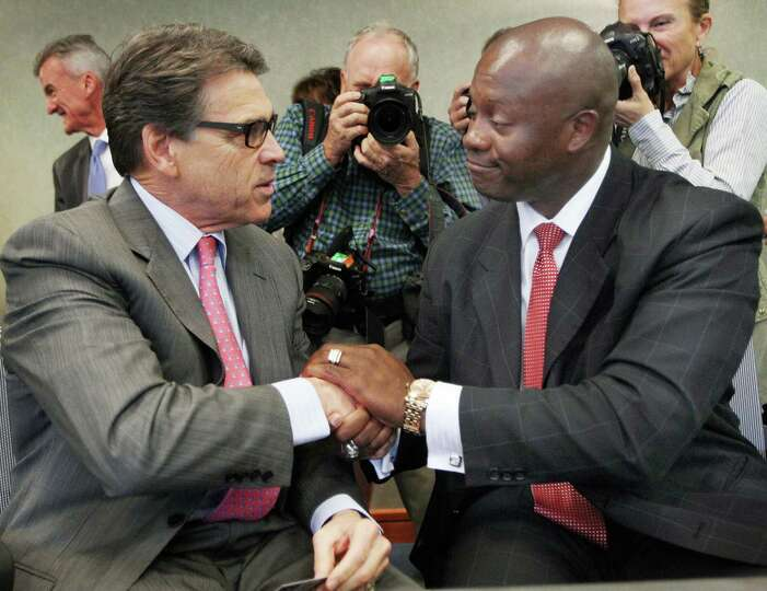 Texas Gov. Rick Perry shakes hands with New Hampshire state Senate hopeful Eddie Edwards after speak