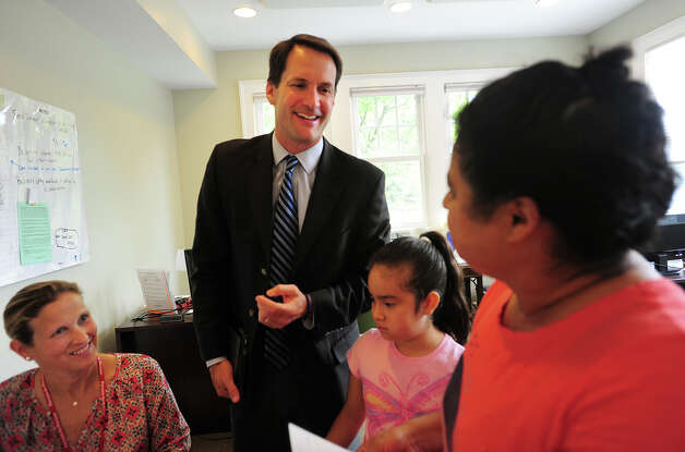 Congressman Jim Himes speaks Spanish with Rosa Raimundo and her granddaughter Ashlie Barrios, 8, both of Stamford, during a visit to Person to Person in Darien, Conn. on Thursday, August 2