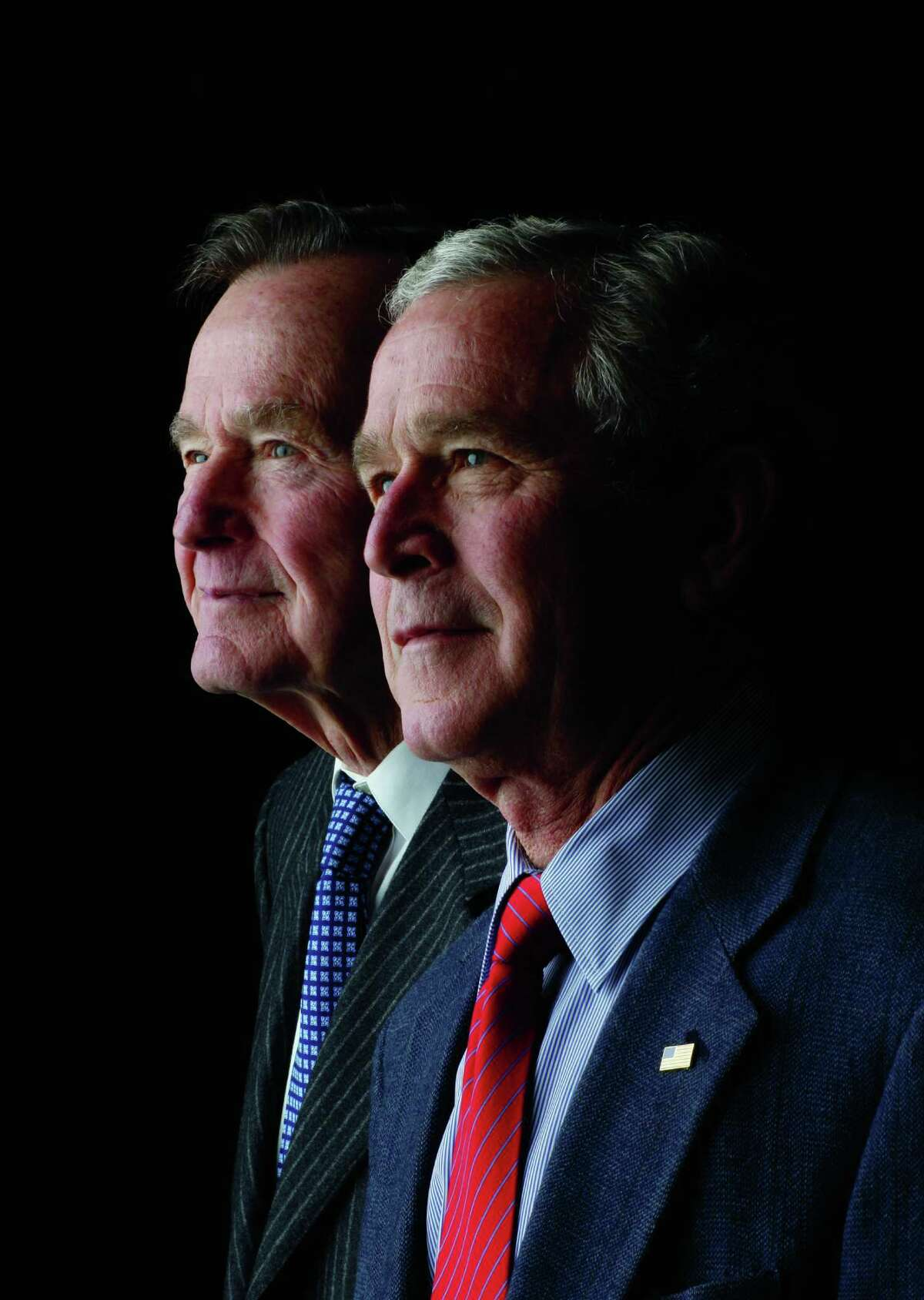 Former President George W. Bush, foreground, has written a biography about his father, former President George H.W. Bush, that is due in November.
