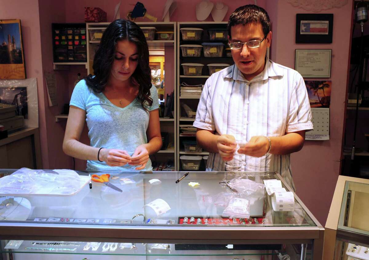 Sandra Zapien, left, and Marcos Mar work with merchandise at Mar Imports on Thursday, Aug. 21, 2014.