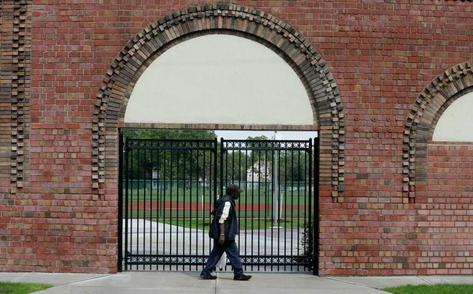 In this Thursday, Aug. 21, 2014 photo, Joe James, 83, walks past an entrance with the original wall at League Park in Cleveland. The city of Cleveland has invested $6.3 million in restoring the old site of League Park, a historic site where the Cleveland Indians clinched their 1920 World Series title, Babe Ruth hit his 500th home run and where Joe DiMaggio extended his hitting streak to 56 games. Not much of the old ballbark, where Cy Young threw the first pitch in 1891 remains, but the new park will host high school and youth games on its all-turf field and will pay homage to the greats who once played there. (AP Photo/Tony Dejak) Photo: Tony Dejak, Associated Press / AP