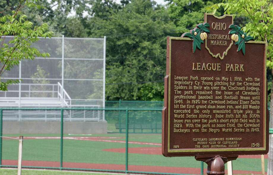 This Thursday, Aug. 21, 2014 photo shows an Ohio Historical Marker plaque commemorating League Park resting near the field in Cleveland. The city of Cleveland has invested $6.3 million in restoring the old site of League Park, a historic site where the Cleveland Indians clinched its 1920 World Series title, Babe Ruth hit his 500th home run and where Joe DiMaggio extended his hitting streak to 56 games. Not much of the old ballbark, where Cy Young threw the first pitch in 1891 remains, but the new park will host high school and youth games on its all-turf field and will pay homage to the greats who once played there. (AP Photo/Tony Dejak) Photo: Tony Dejak, Associated Press / AP