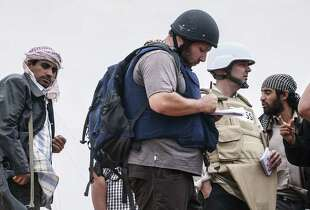 American journalist Steven Sotloff (center, in black helmet) talks to Libyan rebels in this 2011 photo.