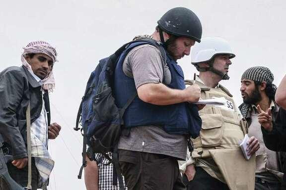 American journalist Steven Sotloff (center, in black helmet) talks to Libyan rebels in this 2011 photo.