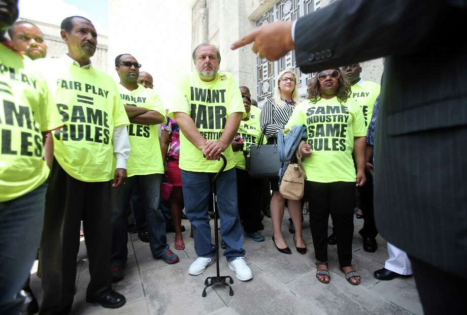 Taxi drivers rallied Aug. 6 outside City Hall after City Council's vote to allow new entrants like Uber and Lyft to operate legally in the city. The proposal saw few changes amended. Photo: Mayra Beltran, Staff / © 2014 Houston Chronicle