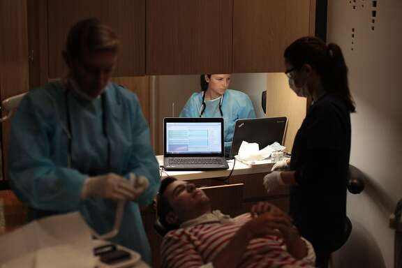 Hygienist Emily Harden, center, prepares her work area for clients at Studio Dental on Wednesday, Aug. 20, 2014 in San Francisco, Calif. Studio Dental parks outside of tech companies such as Facebook, Twitter and Google to offer clients care throughout the day.