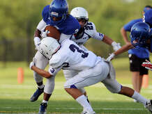 """West Brook's Demarcus Smith, No. 2, is stopped by Port Neches-Groves' Avery Murdock, No. 3, during Friday's scrimmage. The West Brook and Port Neches-Groves high school football teams scrimmaged at the Carrol A. """"Butch"""" Thomas Stadium on Friday afternoon. Photo taken Friday 8/22/14 Jake Daniels/@JakeD_in_SETX"""