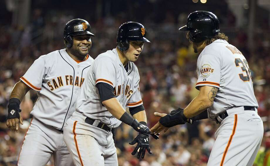 Joe Panik (center) is congratulated by Pablo Sandoval (left) and Michael Morse after his homer. Photo: Evan Vucci, Associated Press