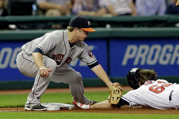 Astros third baseman Matt Dominguez tags out the Indians outfielder Tyler Holt on an attempted steal of third to help squelch a rally in the eighth inning Friday night in Cleveland.