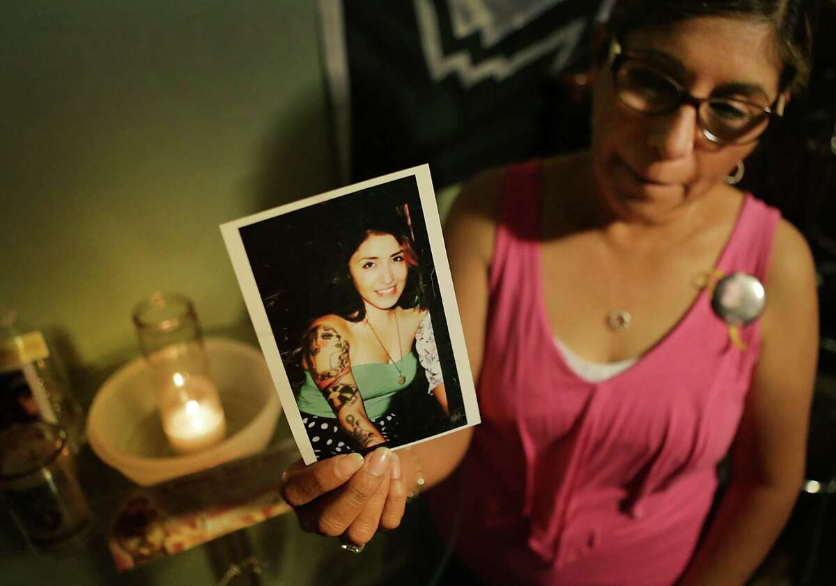 Mary Jimenez holds a photo of her daughter Bianca in front of a small candle-lit shrine near where Bianca's belongings are being kept.