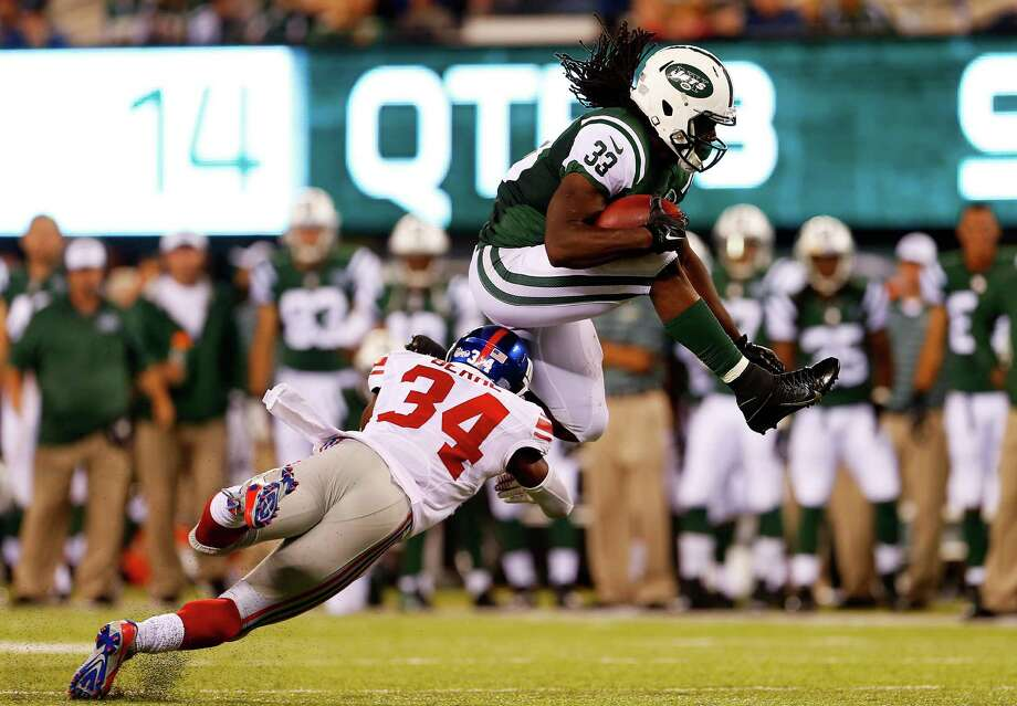 EAST RUTHERFORD, NJ - AUGUST 22:  Chris Ivory #33 of the New York Jets leaps over Nat Berhe #34 of the New York Giants during the third quarter of a preseason game at MetLife Stadium on August 22, 2014 in East Rutherford, New Jersey.  (Photo by Rich Schultz/Getty Images) ORG XMIT: 501567307 Photo: Rich Schultz / 2014 Getty Images