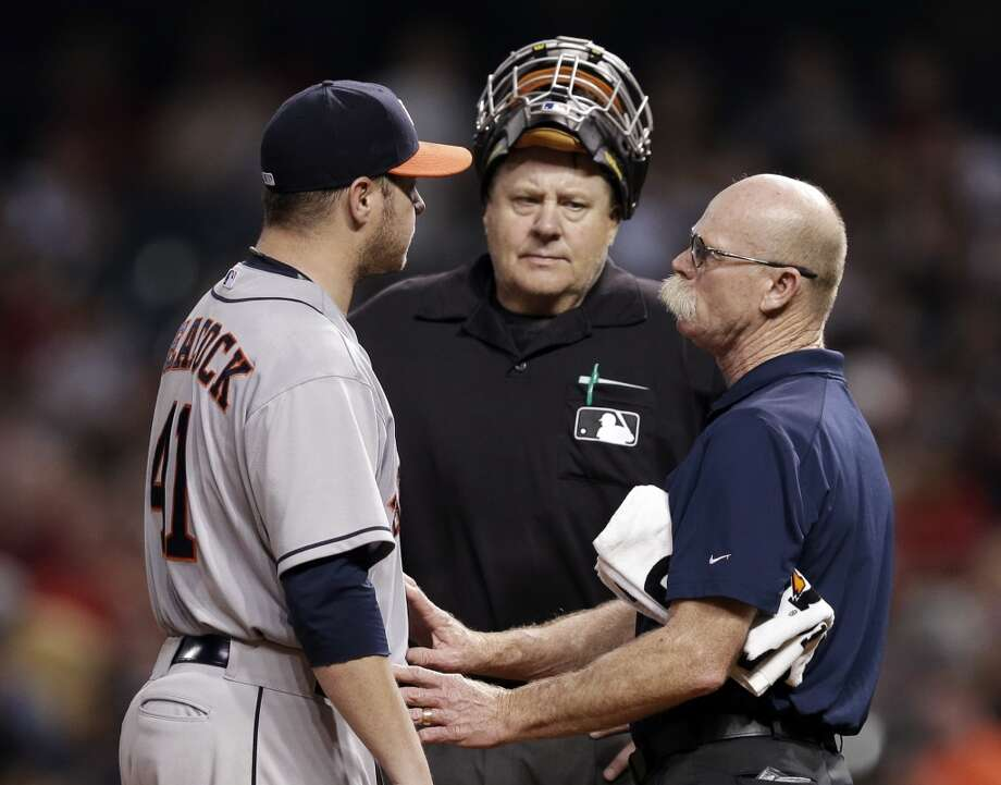 Brad Peacock, left, is checked out by assistant trainer Rex Jones, right, as umpire Gary Cederstrom watches in the sixth inning. Photo: Mark Duncan, Associated Press