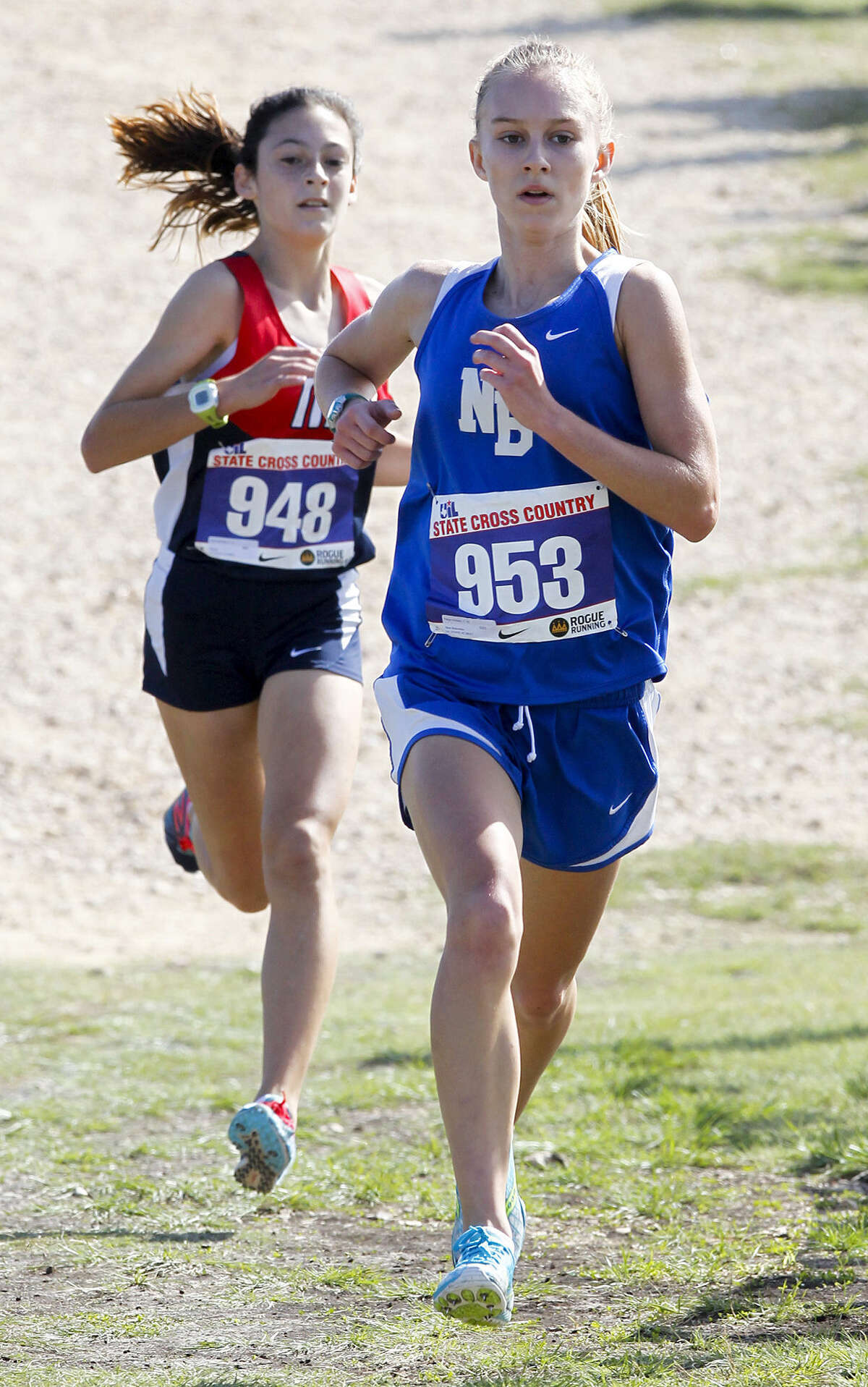 Paige Hofstead of New Braunfels runs ahead of Manvel's Julia Heymach in the 5A girls 5000 meter race during the state cross country meet at Old Settlers Park in Round Rock on Saturday, Nov. 9, 2013. Hofstead finished first overall in the event with a time of 17:36.45 and the Lady Unicorns took second place overall at the meet. MARVIN PFEIFFER/ mpfeiffer@express-news.net
