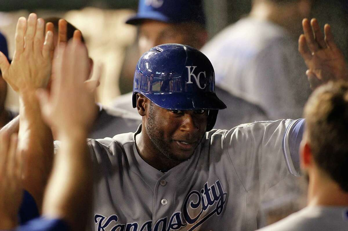 ARLINGTON, TX - AUGUST 22: Lorenzo Cain #6 of the Kansas City Royals is congratulated after scoring against the Texas Rangers in the in the seventh inning at Globe Life Park in Arlington on August 22, 2014 in Arlington, Texas.