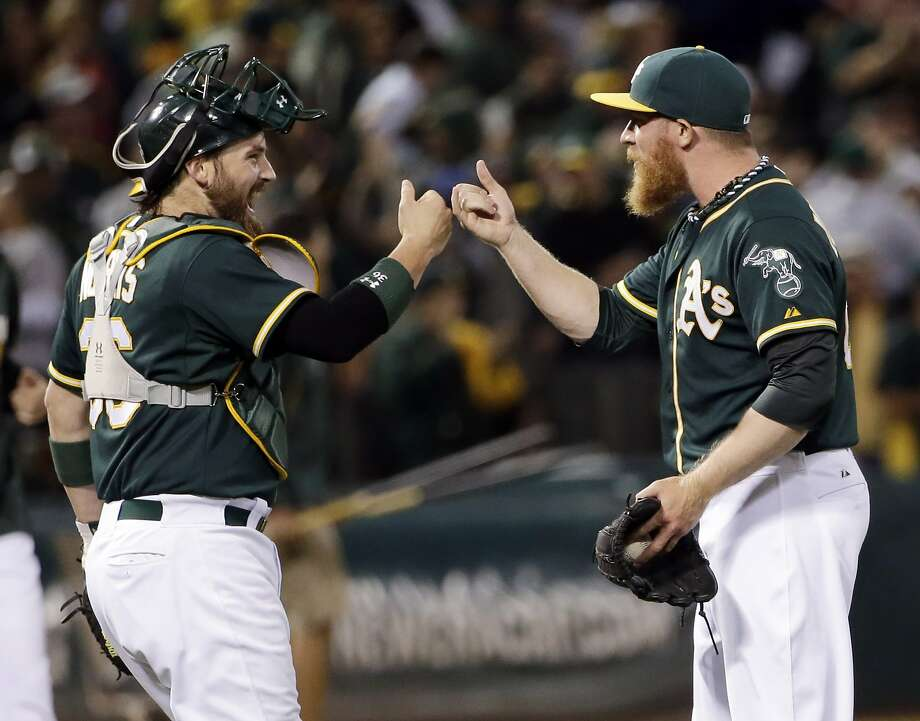 Catcher Derek Norris and closer Sean Doolittle celebrate after a rocky ninth inning that saw Doolittle collect his 19th save. Photo: Marcio Jose Sanchez, Associated Press