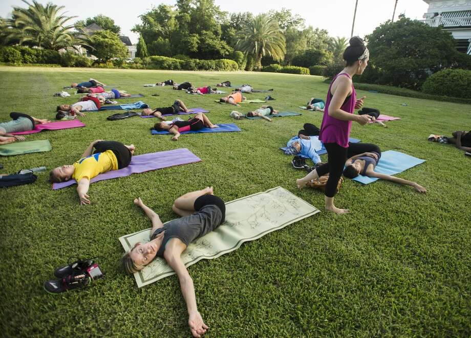 Brandee Perry, front, stretches while Tiffany Maloney, standing, guides Perry and others through stretches during a yoga class at the McFaddin-Ward House on Monday afternoon. Tiffany Maloney of Love Yoga led an outdoor class on the east lawn of the McFaddin-Ward House on Monday afternoon. The monthly class is called Monday at the Museums. Photo taken Monday 6/30/14 Jake Daniels/@JakeD_in_SETX