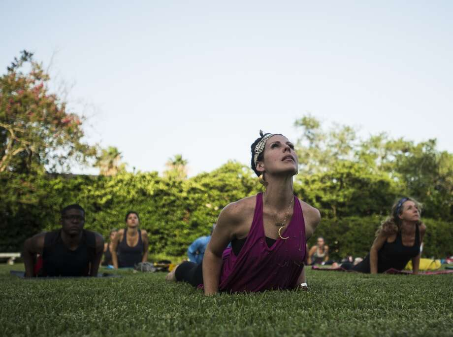 Tiffany Maloney of Love Yoga moves from one position to another as she leads an outdoor class on the east lawn of the McFaddin-Ward House on Monday afternoon. The monthly class is called Monday at the Museums. Photo taken Monday 6/30/14 Jake Daniels/@JakeD_in_SETX
