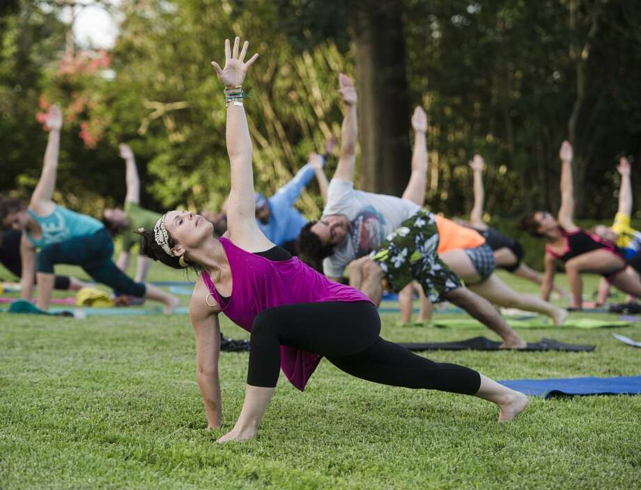 Tiffany Maloney of Love Yoga guides others into a position during an outdoor class on the east lawn of the McFaddin-Ward House on Monday afternoon. The monthly class is called Monday at the Museums. Photo taken Monday 6/30/14 Jake Daniels/@JakeD_in_SETX