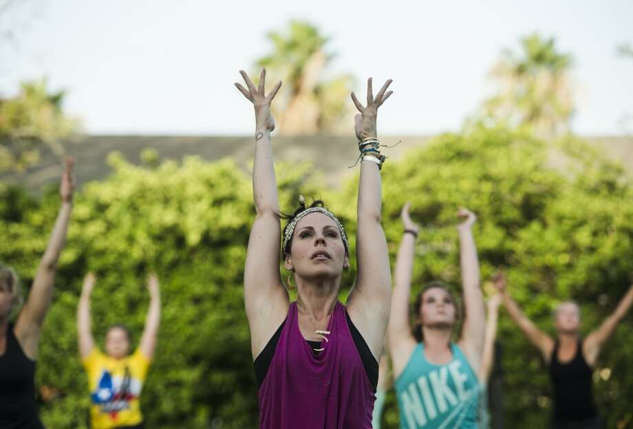 Tiffany Maloney of Love Yoga stretches her arms toward the open sky as she leads an outdoor class on the east lawn of the McFaddin-Ward House on Monday afternoon. The monthly class is called Monday at the Museums. Photo taken Monday 6/30/14 Jake Daniels/@JakeD_in_SETX