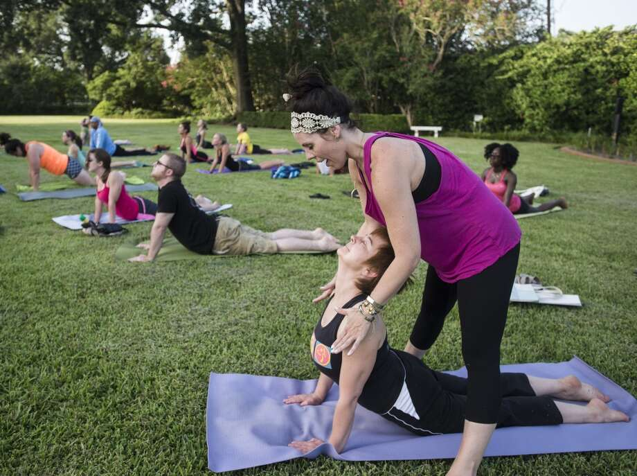 Tiffany Maloney of Love Yoga helps position Elena Ivanova in a stretch during an outdoor class on the east lawn of the McFaddin-Ward House on Monday afternoon. The monthly class is called Monday at the Museums. Photo taken Monday 6/30/14 Jake Daniels/@JakeD_in_SETX