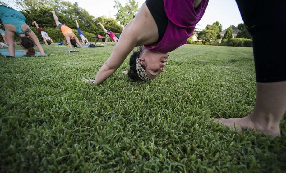 Tiffany Maloney of Love Yoga leads an outdoor class on the east lawn of the McFaddin-Ward House on Monday afternoon. The monthly class is called Monday at the Museums. Photo taken Monday 6/30/14 Jake Daniels/@JakeD_in_SETX