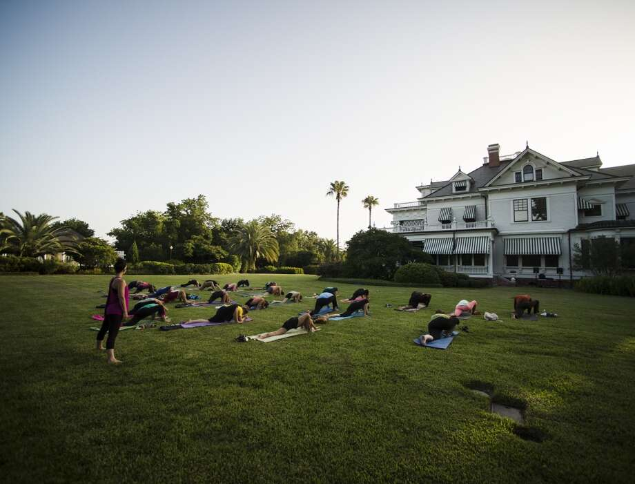 Tiffany Maloney of Love Yoga, left, looks over stretch yoga practitioners during an outdoor class on the east lawn of the McFaddin-Ward House on Monday afternoon. The monthly class is called Monday at the Museums. Photo taken Monday 6/30/14 Jake Daniels/@JakeD_in_SETX