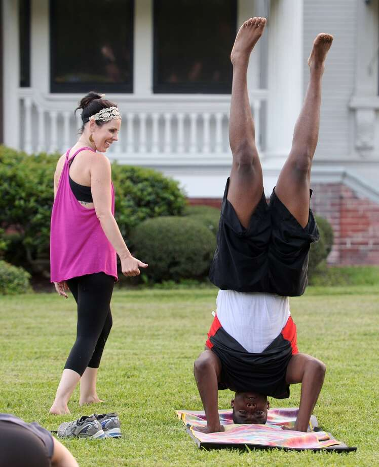 Tiffany Maloney of Love Yoga gives a thumbs up to Ronnie Turner as he practices a headstand Monday. Maloney led an outdoor class on the east lawn of the McFaddin-Ward House on Monday afternoon. The monthly class is called Monday at the Museums. Photo taken Monday 6/30/14 Jake Daniels/@JakeD_in_SETX