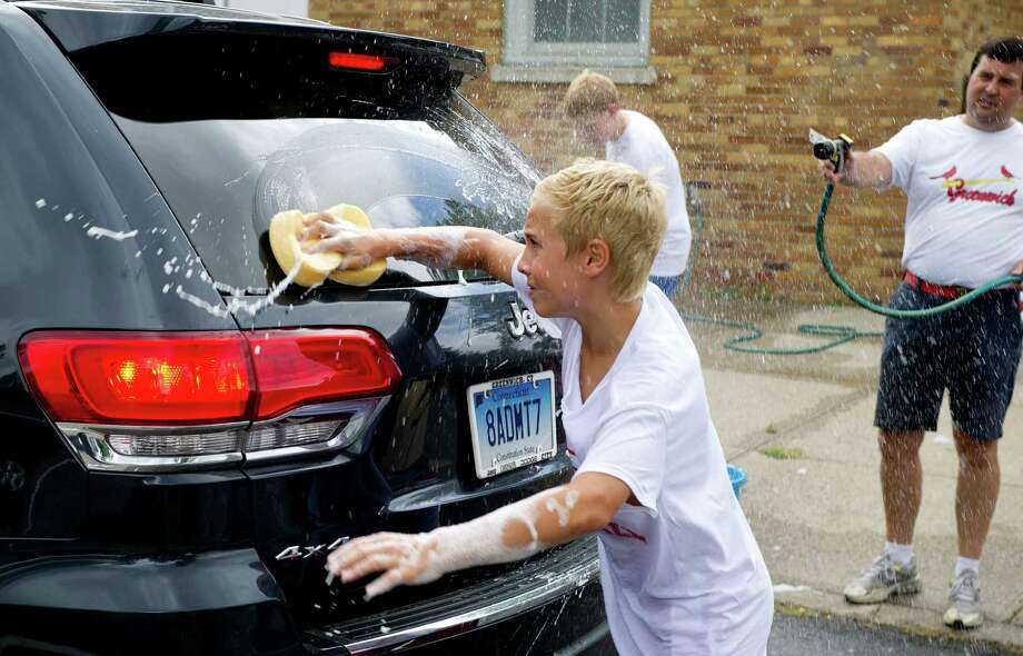 Greenwich High School football team member Harlan Giordano, 14, helps wash cars to raise money for the team's booster club at Old Greenwich School on Saturday, August 23, 2014. Photo: Lindsay Perry / Stamford Advocate