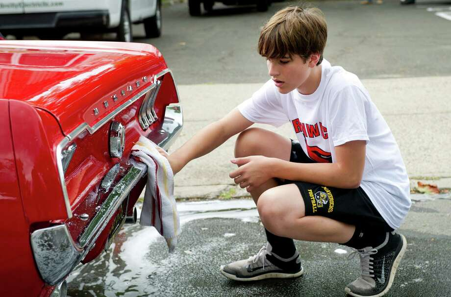 Greenwich High School football team member Tyler Blizzard, 14, helps wash Stephanie Chow's 1967 Mustang during a car wash to raise money for the team's booster club at Old Greenwich School on Saturday, August 23, 2014. Photo: Lindsay Perry / Stamford Advocate