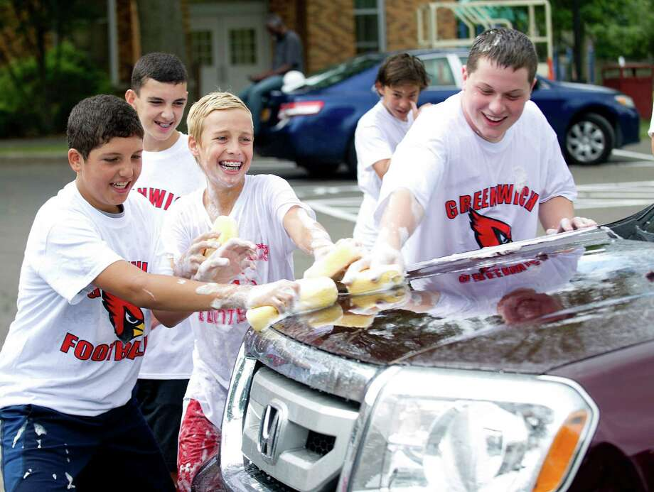 From left, Greenwich High School football team members Rodrigo Blanco, Harlan Giordano, and John Duffy, all 14, wash cars to raise money for their booster club at Old Greenwich School on Saturday, August 23, 2014. Photo: Lindsay Perry / Stamford Advocate